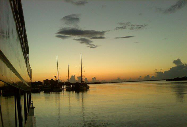 image of boats anchored in back bay of Fort Myers Beach at dusk taken from excursion boat
